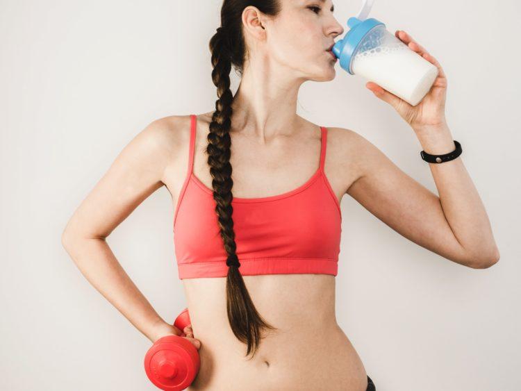 女性がプロテインを飲む画像